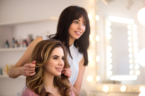Natural beauty. Professional cheerful hairdresser holding hair of her client while showing her new hairstyle.
